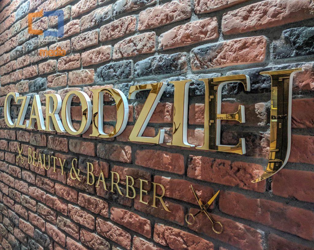 logo ze złotych liter na ścianę